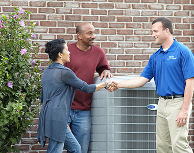 HVAC technician discussing repairs with the homeowners