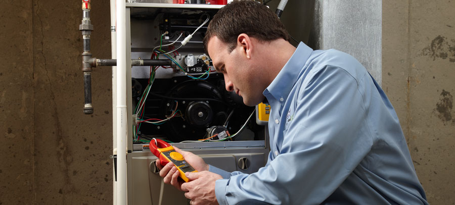 HVAC technician performing furnace maintenance and cleaning services