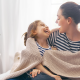 Mother and daughter snuggle up in blanket and enjoy health benefits of a humidifier.