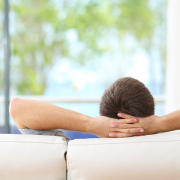 Man relaxes on white couch in living room and considers benefits of ductless vs central air conditioning.