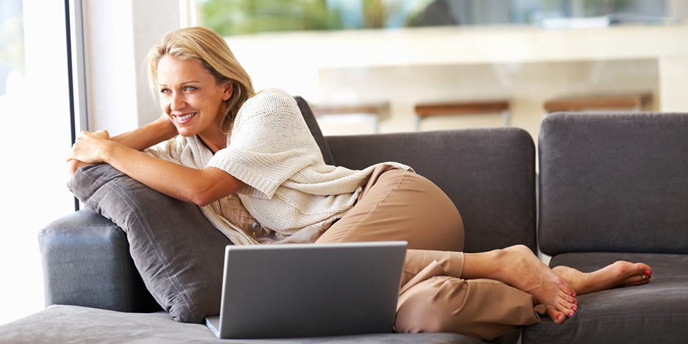 Woman relaxes on grey couch after completing spring HVAC checklist.