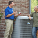 HVAC tech meets with homeowner in his backyard to install a new air conditioner.