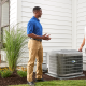 Technician in blue shirt explains to homeowner how air conditioner maintenance is helpful.